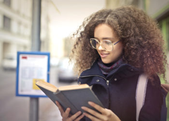 Student reading book by bus stop